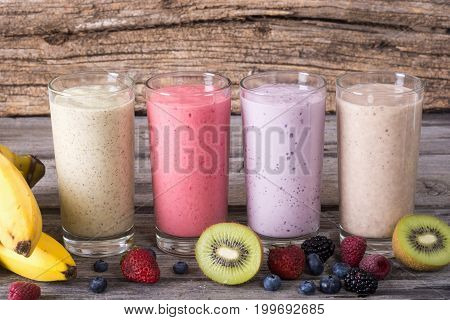 Milk shake with berries and fruit on wooden background