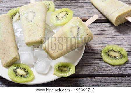 Homemade kiwi popsicle withe ice . Space for text