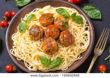 Spaghetti in plate with meatballs and basil