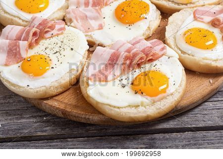 Sandwich with eggs and bacon on wooden table