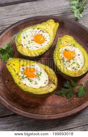 Baked avocado with eggs on woode background