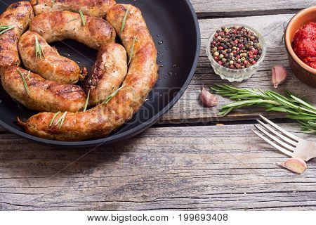 Homemade grilled sausages in pan with rosemary .