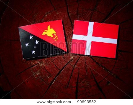 Papua New Guinea Flag With Danish Flag On A Tree Stump Isolated