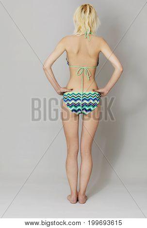 Attractive young woman standing in bikini in studio.