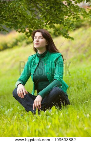 Happy Young Woman Sitting On Grass