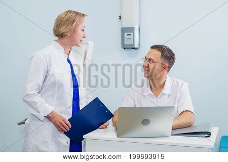 Doctor having conversation with his colleague and holding xray in medical office.