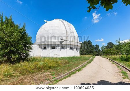 The road next to the Observatory building with a retractable dome for the coronograph. The dome of the telescope during the day.