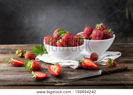 Ripe strawberry in a bowl on a wooden board on a dark background