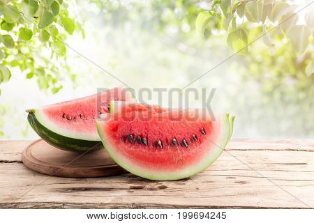 Ripe cut watermelon on a wooden table on a background of green leaves