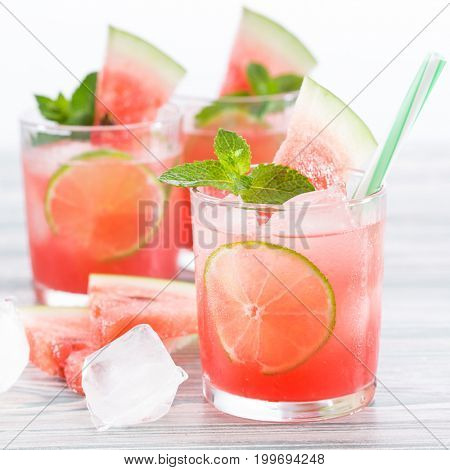 Summer cold drink with watermelon, mint and lemon on a wooden background