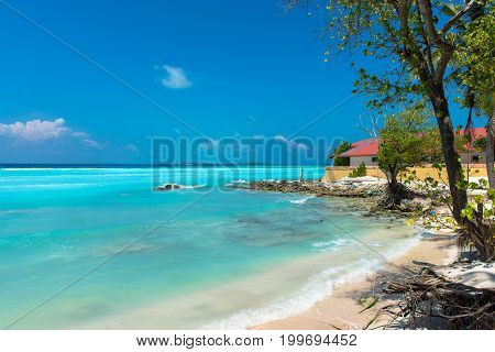 Horizontal picture of Maafushi's beach with beautiful turquoise water and roots. House beachfront in the amazing Maldives.