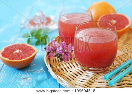 Grapefruit pulp juice in two glasses and grapefruit halves