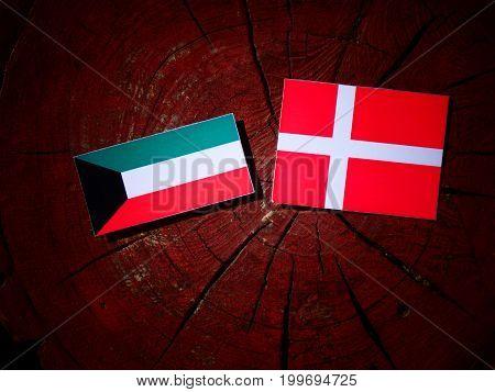 Kuwaiti Flag With Danish Flag On A Tree Stump Isolated