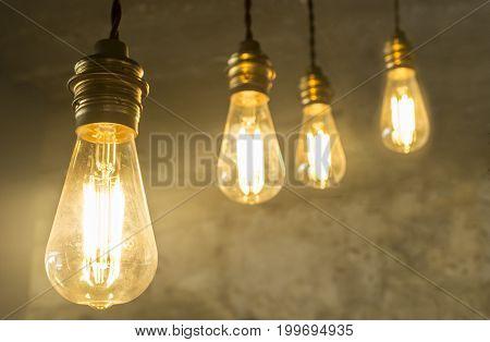 Four hanging light bulbs over oxide dark color concrete background. Closeup