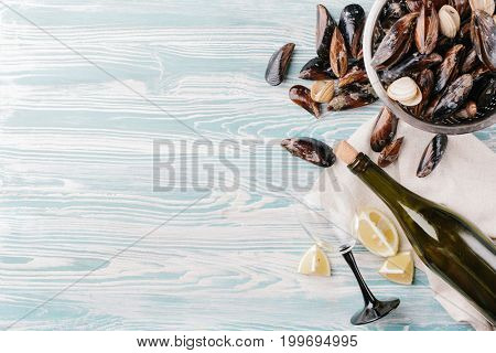 Shells of washed mussels in a colander and slices of lemon and a bottle of wine on a wooden background. Top view. Copy space.
