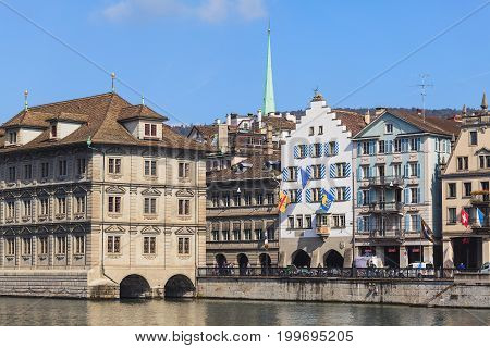 Zurich, Switzerland - 2 October, 2014: embankment of the Limmat river, old town buildings along it, the leftmost one is the Zurich town hall. Zurich is the largest city in Switzerland and the capital of the Swiss canton of Zurich.