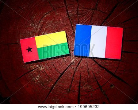 Guinea Bissau Flag With French Flag On A Tree Stump Isolated