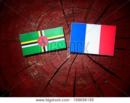 Dominica Flag With French Flag On A Tree Stump Isolated