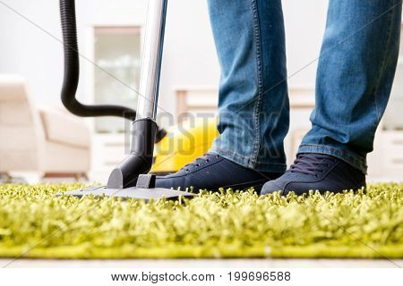 Man cleaning the floor carpet with a vacuum cleaner close up