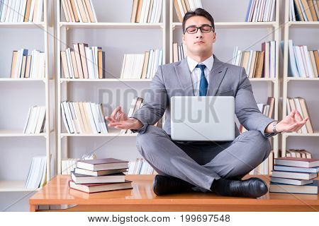 Businessman student in lotus position meditating with a laptop i