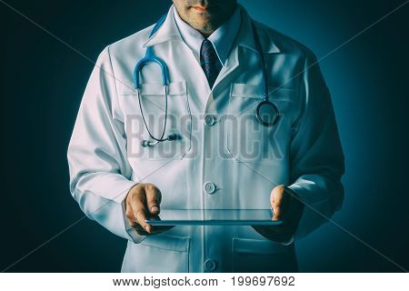 Doctor with stethoscope and tablet computer on black background still life style Technology to treat patients concept.