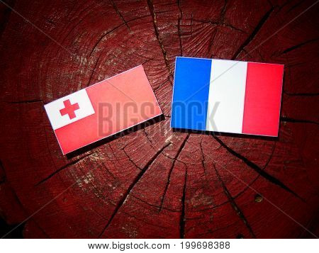 Tonga Flag With French Flag On A Tree Stump Isolated
