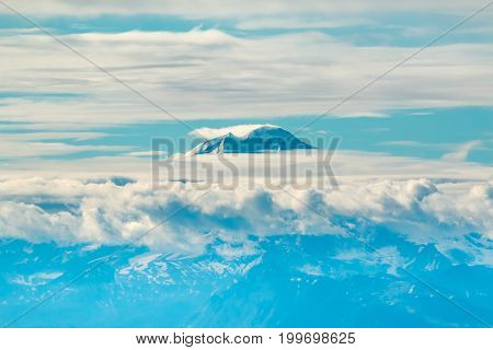 The tip of Mt Iliamna Volcano peeking through the clouds