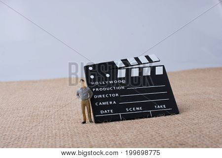 Movie clapper and a man figurine on a canvas