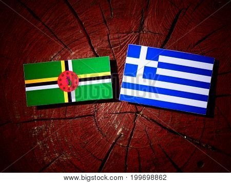 Dominica Flag With Greek Flag On A Tree Stump Isolated