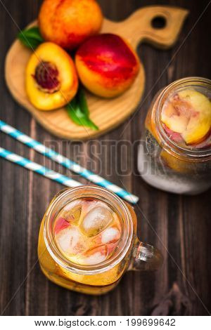 Mason Jar Glass Of Homemade Peach Iced Water On A Rustic Wooden Background. Top View.