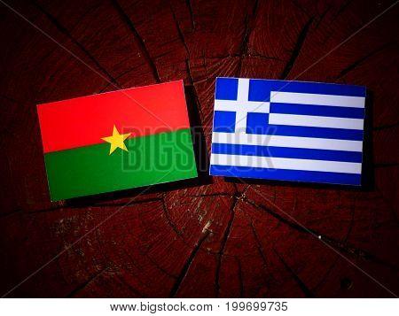 Burkina Faso Flag With Greek Flag On A Tree Stump Isolated
