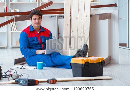 Young carpenter with a laptop computer
