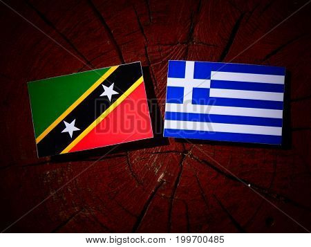 Saint Kitts And Nevis Flag With Greek Flag On A Tree Stump Isolated