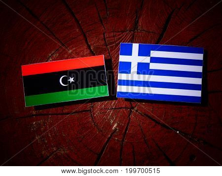 Libyan Flag With Greek Flag On A Tree Stump Isolated