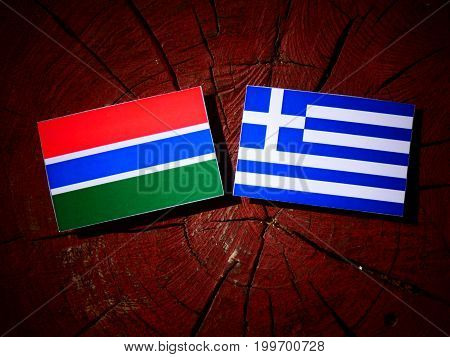 Gambian Flag With Greek Flag On A Tree Stump Isolated