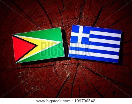 Guyana Flag With Greek Flag On A Tree Stump Isolated