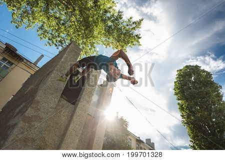 City parkour. The guy does the opposite somersault. Shooting from the lower angle. Dexterity and extreme.