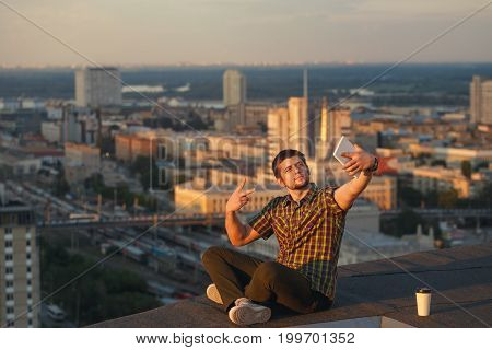 A hipster guy makes a selfie on the roof of a high-rise building. The blogger has conquered a new height. The video blogger broadcasts live from the roof.