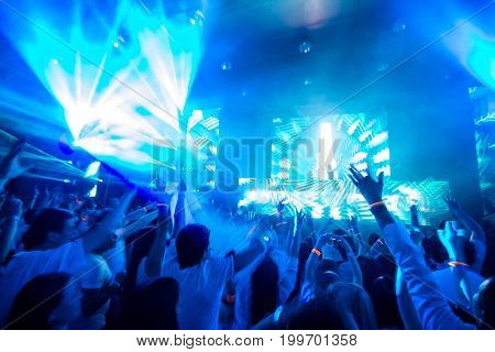 Young people dancing, clapping, happy, hands up in a laser light show and acid music, plays the famous DJ. In blue tones.