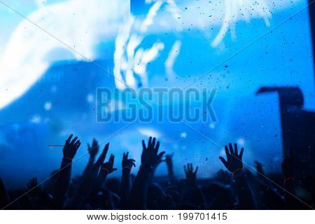 Silhouette of raised hands spectators on background beautiful light show. Blue background, large screen monitor, confetti.