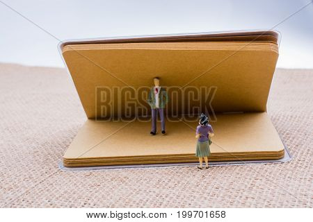 Figurine Of Man And Woman With A Notebook