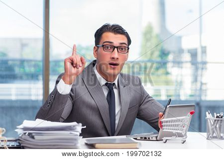 Businessman with shopping cart in office