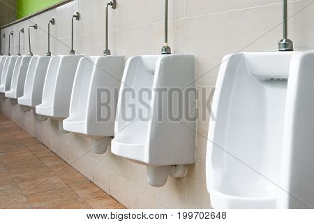 White urinal in men's bathroom. . .