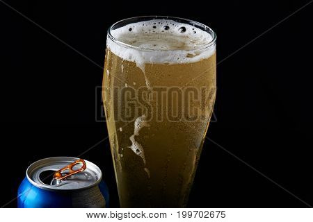 Cold beer in glass from metal can isolated on black background