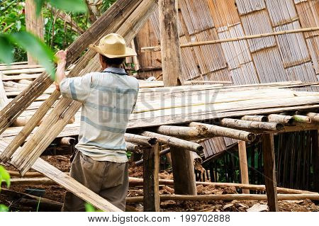 Local area farmer building his own house with simple bamboo wood style.