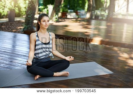 Morning yoga practice outdoors is the healthy start of a new day. Woman sitting in easy pose for meditation outdoors.