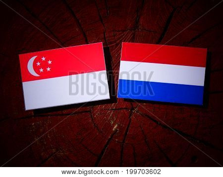 Singaporean Flag With Dutch Flag On A Tree Stump Isolated