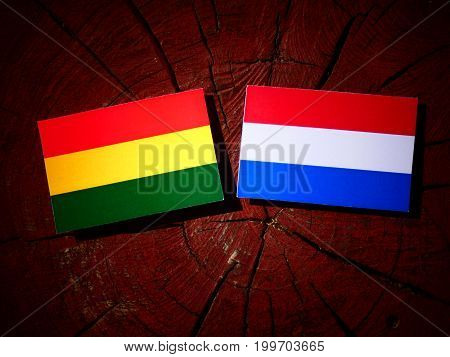 Bolivian Flag With Dutch Flag On A Tree Stump Isolated