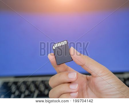 Closeup hand holding memory card with laptop background.