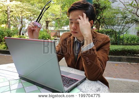 Tired young business man holding glasses and suffering eyestrain in front of screen laptop at outdoor park.